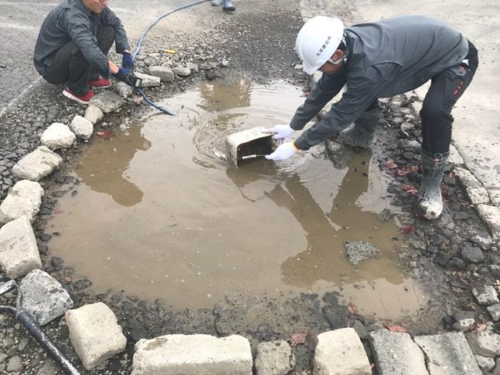 駐車場の水溜まりアスファルト補修工事。泥水を除去する様子