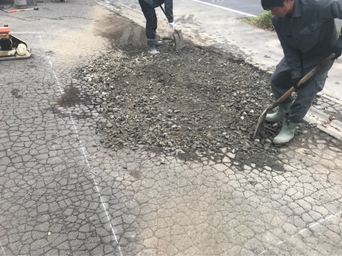 駐車場の水溜まりアスファルト補修工事。路盤材を補充している様子