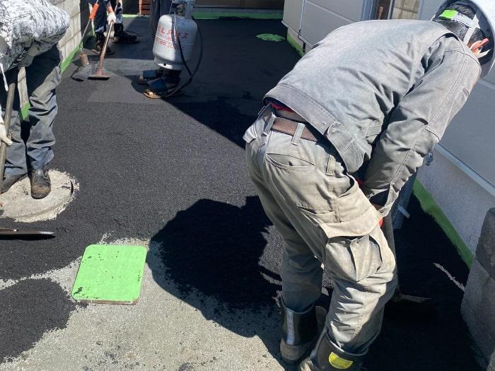 北区玄関前通路ロードヒーティング工事(アスファルト舗装敷設作業中)
